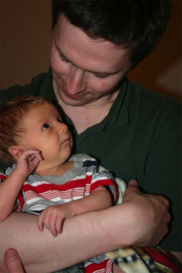 <p>Aaron holding Christian, while Christian looks at him</p>