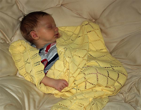 <p>Christian sleeping in the papasan with his yellow blanket</p>